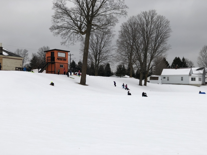 Sledding on the football field hill.